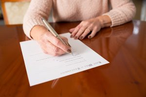 Lady Signing Last Will And Testament